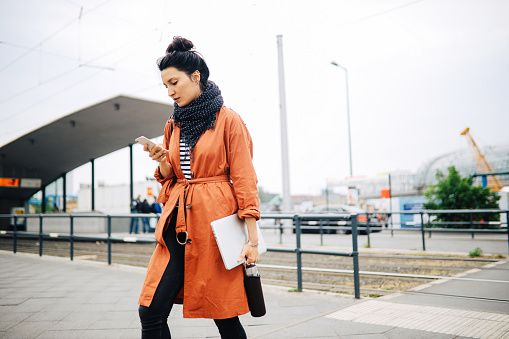 young commuter woman, walking in berlin, carrying her laptop, checking apps on the mobile phone
