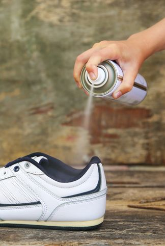female hand holding a spray deodorant for shoes