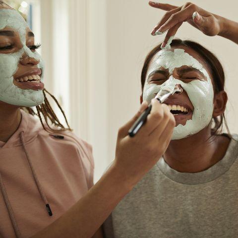 Young woman enjoying friend's applying cream on face