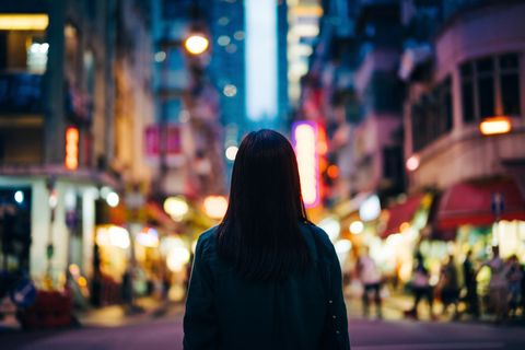 rear view of young woman in the city standing against the illuminated city street at dusk