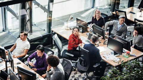 an aerial view of a modern office environment with people sitting at desks, working at computers