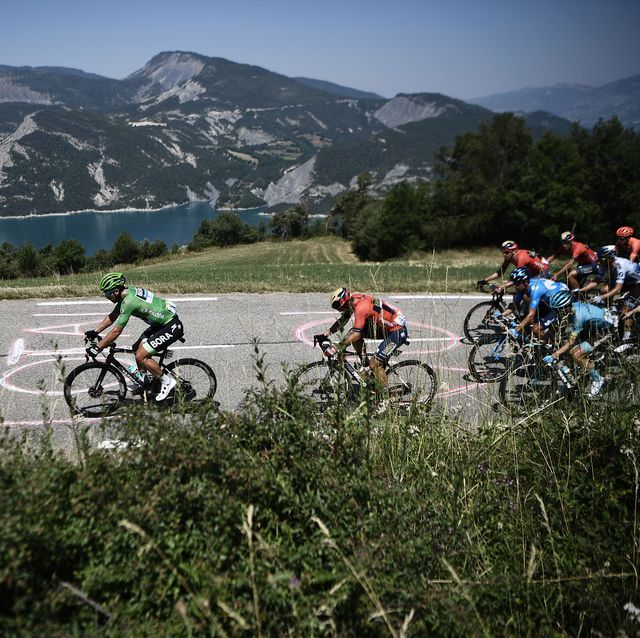 slovakias peter sagan l, wearing the best sprinters green jersey and the pack pass by the lac of serre poncon serre poncon lake during the eighteenth stage of the 106th edition of the tour de france cycling race between embrun and valloire, in valloire, on july 25, 2019 photo by anne christine poujoulat  afp        photo credit should read anne christine poujoulatafp via getty images
