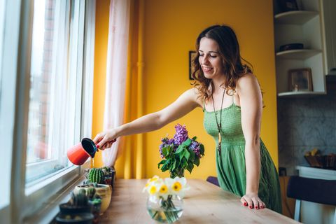 young caucasian woman watering plants next to a window sill