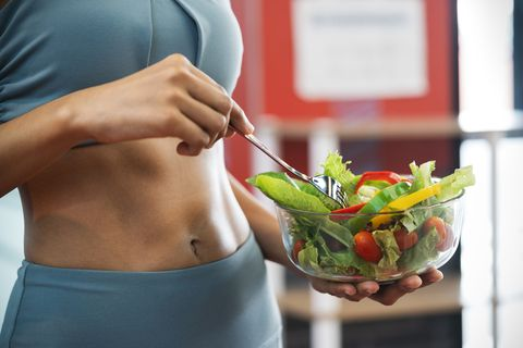 close up of a sport woman with her sexy belly, she holding a bowl of fresh healthy food