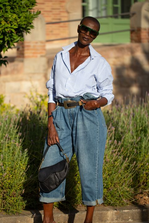 barcelona, spain   june 27 a guest is seen on the street attending 080 barcelona fashion week wearing blue shirt, high waisted blue jeans, black belt and black dior bag on june 27, 2019 in barcelona, spain photo by matthew sperzelgetty images