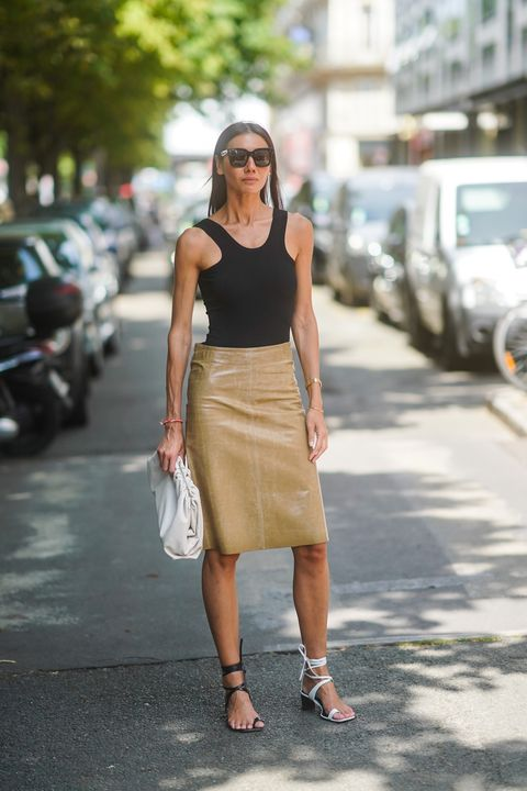 paris, france   july 01 julia pelipas wears sunglasses, a black top, a shiny light camel leather skirt, a large white clutch, different colors gladiator sandals  white and black, outside dior, during paris fashion week  haute couture fallwinter 20192020, on july 01, 2019 in paris, france photo by edward berthelotgetty images