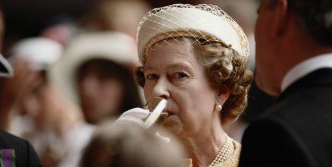 Queen Elizabeth II drinking a glass of champagne on-board HMS Invincible