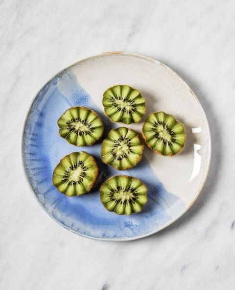 Slices of kiwi on a plate on white background