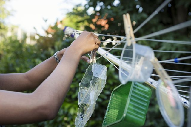 young woman hanging washed plastic containers onto a clothesline to dry