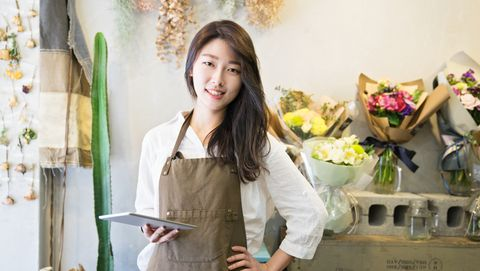 small business owner holding digital tablet looking at camera