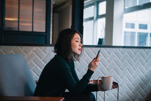 mujer mirando el móvil con un cafÉ