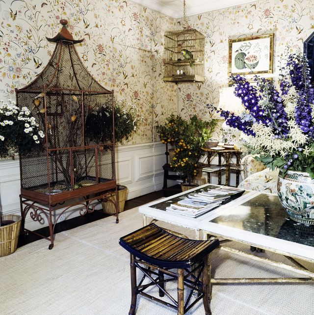 a room in the country home of prince stanislaw and princess lee radziwill, turville grange, buckinghamshire, england a floral fabric covers the walls of the room cast iron legs shaped like bamboo support a coffee table on which several magazines and a round ceramic vase of flowers are displayed on the walls hang nineteenth century watercolors of fruits and vegetables a large victorian birdcage stands against the left wall and holds yellow orange canaries suspended from the ceiling in the corner of the room is a smaller gold cage holding a green parrot   local caption