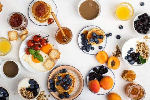 healthy vegetarian breakfast or brunch, favorite meal homemade granola with yoghurt, pancakes, fried eggs, fresh summer fruits, berries, coffee and juice, honey on light gray table viewed from above