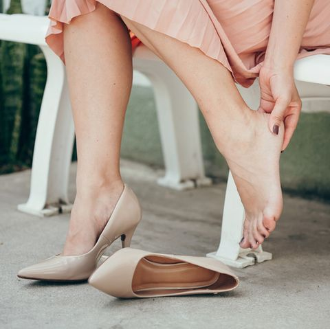 woman suffering from leg pain outdoors because of uncomfortable shoes