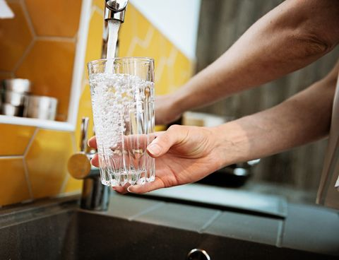 woman filling a glass with filtered water right from the tap