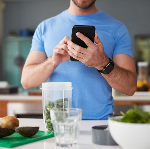 close up of man using fitness tracker to count calories for post workout juice drink he is making