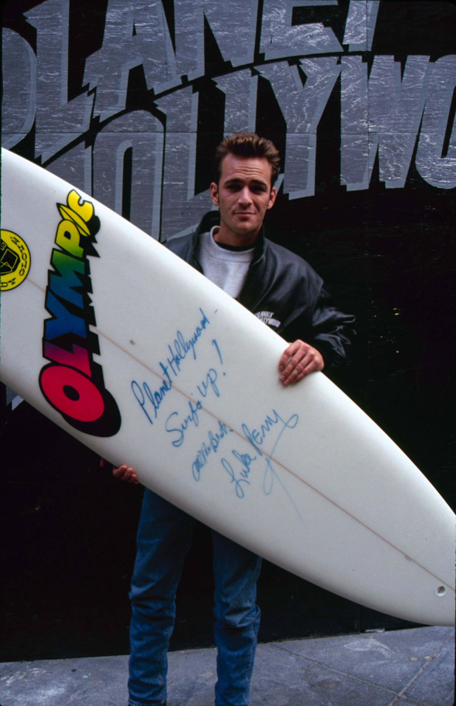 Perry holds an autographed surfboard in 1990.