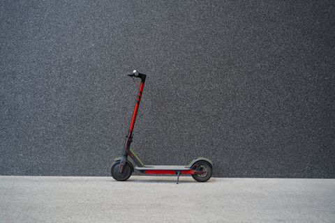e scooter next to black modern wall, no people