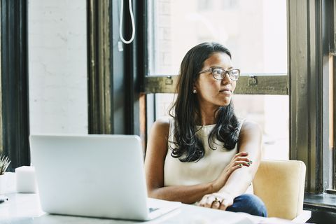 Businesswoman looking out window while seated at desk in office