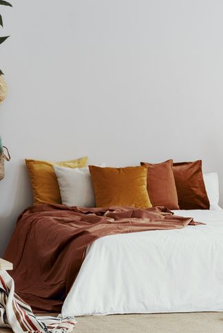 Autumn colored pillows on king size bed in chic bedroom interior