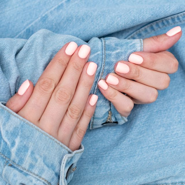 manicure in coral color on denim background