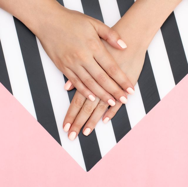 Stylish trendy female white, black and blue manicure. Beautiful young woman's hands on pink and white background.