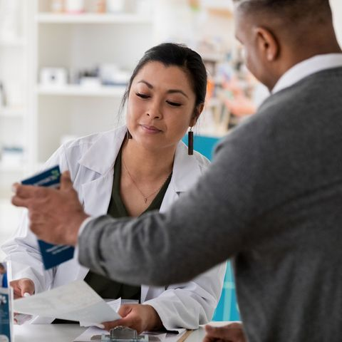 Male pharmacy customer asks question in pharmacy