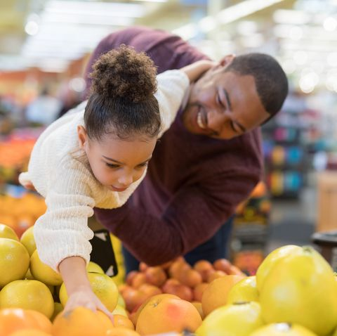 a pre school age girl helps her parents pick out veggies and fruit in the produce section at the grocery store her dad is playfully holding her up in the air so she can pick out an orange