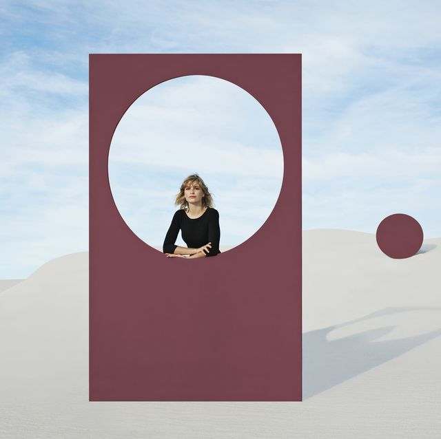 portrait of young woman standing by maroon portal at white desert against sky