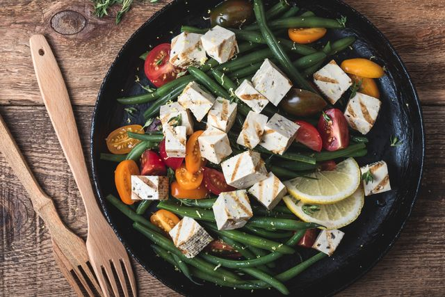 delicious summer vegan meal, healthy green beans salad with grilled tofu, fresh colorful mix cherry tomatoes, thyme herbs and lemon zest served in rural cast iron skillet, wooden forks, top view