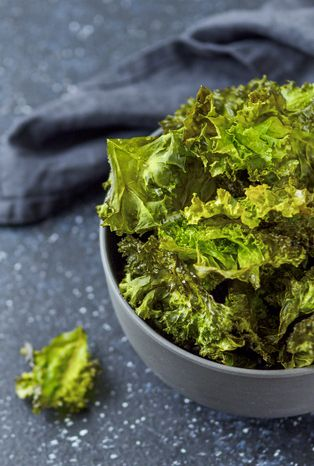 green kale chips with salt in bowl homemade healthy snack for low carb, keto, low calorie diet dark blue background ready to eat kale chips, copy space left banner