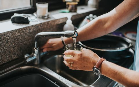 person at a tap, filling a glass of water
