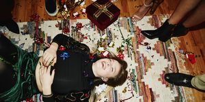 Laughing woman lying on floor covered in bows and confetti during holiday party with friends