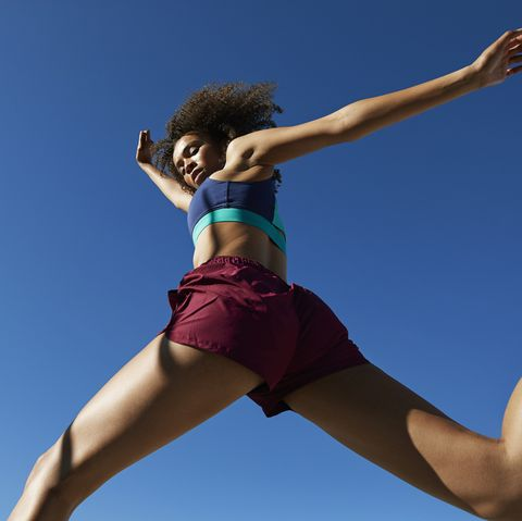 frizzy young female athlete jumping against clear blue sky on sunny day