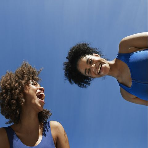 directly below shot of cheerful female sportspeople against blue sky during sunny day