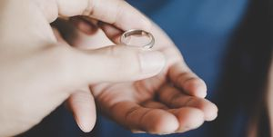 A young couple's hands holding a wedding ring, a concept of divorce