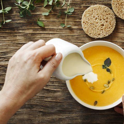 Pumpkin creamy soup on dark wooden background