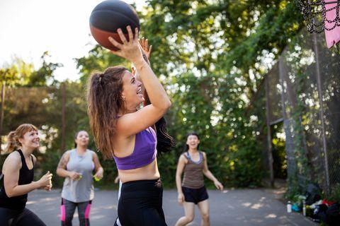 Multi-ethnic female friends having fun playing streetball