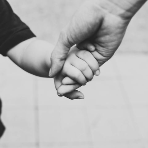 a young mother and a toddler is walking at the park while holding hands