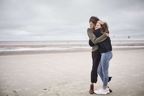 Happy young woman hugging girl on the beach