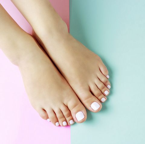 Female legs with white pedicure on pink and blue background, top view