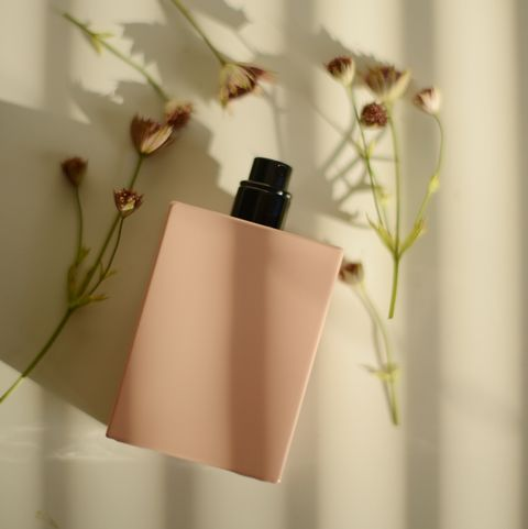 pink perfume bottle and some widlfowers on a white background in a beautiful sunlight coming through blinds