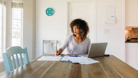 a woman sits at her dining room table with laptop and financial reports doing her monthly budget she is writing down budgets as she works on her computer to do monthly finances, pay taxes and save money for the future