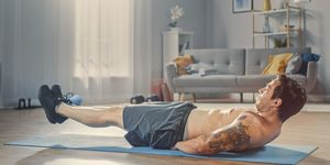 Strong Athletic Shirtless Fit Man in Grey Shorts is Doing Abdominal Exercises at Home in His Spacious and Sunny Living Room with Minimalistic Interior.