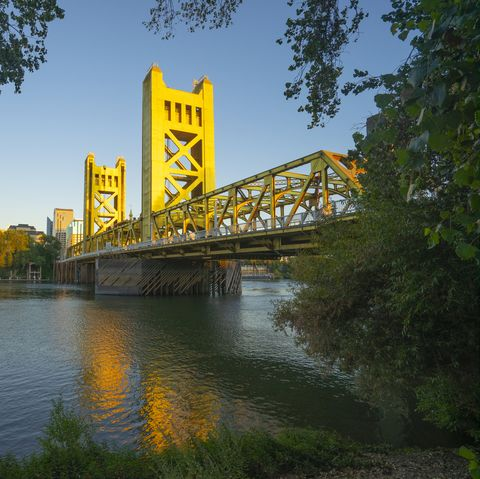 tower bridge and sacramento, california downtown skyline reflecting in sacramento river