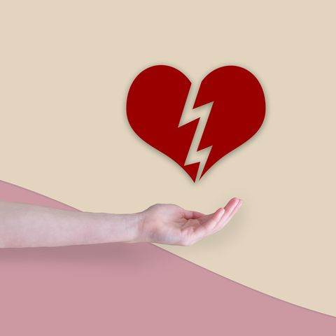 arm in front of a two colored background with a red broken valentine heart floating above the hand love  health concept