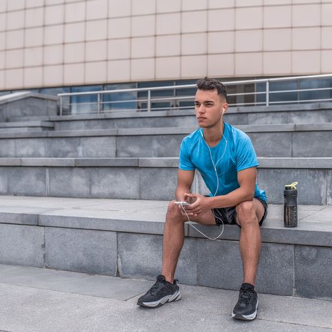 Athletic male athlete, summer city sitting hand, listening to phone music headphones motivation fitness sport training, shaker protein, morning workout.  Active lifestyle young people, powerful stylish man.