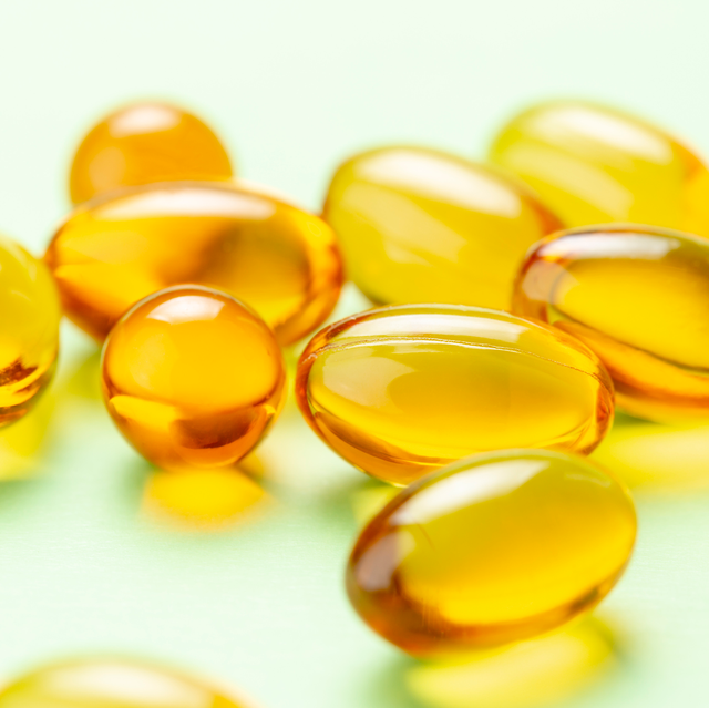 golden vitamin d supplements on green background