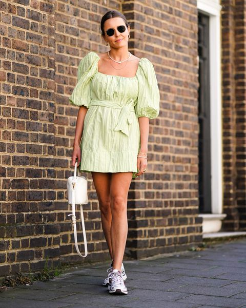 london, england   september 14 a guest wears sunglasses, a necklace, a white bag, a pale green dress with puff shoulders, sneakers shoes, during london fashion week september 2019 on september 14, 2019 in london, england photo by edward berthelotgetty images
