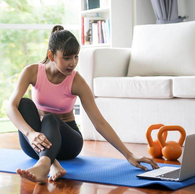 young woman watching yoga videos at home